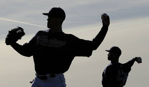 photo - San Diego Padres pitchers Clayton Richard, left, and Fautino De Los Santos throw during a spring training baseball workout on Friday, Feb. 15, 2013, in Peoria, Ariz. (AP Photo/Charlie Riedel)