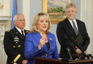 photo - Gov. Mary Fallin announces Thursday that Oklahoma is the first state to be chosen by the federal government to test drones for public safety purposes. Maj. Gen. Myles Deering, state adjutant general, left, and Stephen McKeever, Secretary of Science and Technology on the governors Cabinet, listen. PHOTO BY PAUL B. SOUTHERLAND, THE OKLAHOMAN
