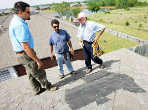 photo - Jim Beres, right, and Allen Vollmer, middle, both with Good Guys Construction, on Tuesday show Eric Ingram, owner of Aegis Roofing, temporary roof repairs made to a home in Moore.  The home was damaged in the severe weather Monday. Photos by Nate Billings, The Oklahoman