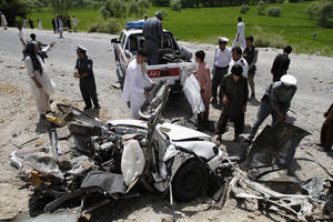Photo -   Afghans look at the wreckage of a vehicle after a roadside explosion on the outskirts of Laghman province east of Kabul, Afghanistan, Sunday, Aug. 12, 2011. A provincial spokesman says a roadside bomb has killed a district chief in eastern Afghanistan and three of his bodyguards. (AP Photo/Rahmat Gul)