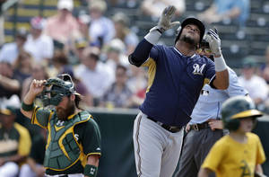 Photo - Milwaukee Brewers' Juan Francisco, right, looks skyward after hitting his second home run of the day as Oakland Athletics catcher Derek Norris, left, looks on during the second inning of a spring training baseball game on Thursday, Feb. 27, 2014, in Scottsdale, Ariz. (AP Photo/Gregory Bull)