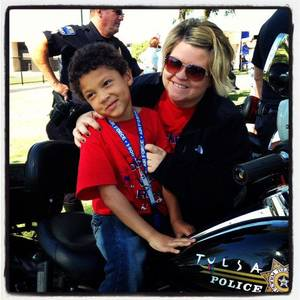 Photo - Kannon Cooper sits on a Tulsa Police officer's motorcycle at the Buddy Walk for Down Syndrome a his mom, Andee Cooper, holds him steady. Kannon suffers from pediatric epilepsy. Photo provided. <strong></strong>