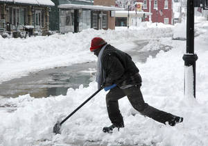 photo - James Smith clears snow from sidewalks Tuesday, Feb. 26, 2013, in downtown Sedalia, Mo., which received about a foot of snow overnight. The second major snowstorm in a week battered the nation's midsection Tuesday, dropping a half-foot or more of snow across Missouri and Kansas with gusting winds blew drifts more than 2 feet high creating  treacherous driving conditions for those who dared the morning commute.(AP Photo/The Democrat, Bob Satnan)