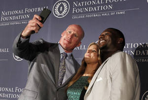 Photo - Former Penn State linebacker Shane Conlan, left, and former TCU tailback LaDainian Tomlinson, right, pose for selfie with event emcee Bonnie Bernstein, center, after Conlan and Tomlinson were introduced as 2014 inductees at a National Football Foundation College Football Hall Of Fame news conference, Thursday, May 22, 2014, in Irving, Texas. (AP Photo/Tony Gutierrez)