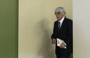 "Photo - Formula One boss Bernie Ecclestone leaves the courtroom on the third day of his trial in the regional court in Munich, Germany, Friday, May 9, 2014. Ecclestone is charged with bribery and incitement to breach of trust ""in an especially grave case"" over a US dollar 44 million payment to a German banker, that prosecutors allege was meant to facilitate the sale of the Formula One Group to a buyer of Ecclestone's liking. (AP Photo/Matthias Schrader)"