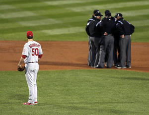 Photo - FILE - In this Oct. 23, 2013, file photo, St. Louis Cardinals starting pitcher Adam Wainwright watches as umpires discuss a ruling during the first inning of Game 1 of baseball's World Series against the Boston Red Sox in Boston. Major League Baseball announced Thursday, Jan. 16, 2014, that it will greatly expand instant replay to review close calls starting this season. Each manager will be allowed to challenge at least one call per game. If he's right, he gets another challenge.  After the seventh inning, a crew chief can request a review on his own. (AP Photo/Charles Krupa, File)