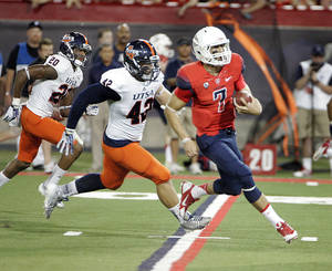 Photo - Arizona's starting quarterback B.J. Denker (7) runs pass Texas San Antonio's Jens Jeters (42) and Andre Brown (20) for a touchdown in the first quarter of an NCAA Football game in Tucson, Ariz. on Saturday Sept. 14, 2013. (AP Photo/Wily Low)