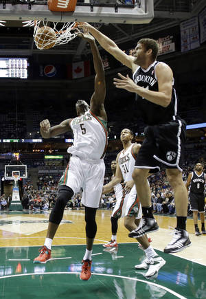 Photo - Brooklyn Nets' Brook Lopez dunks over Milwaukee Bucks' Ekpe Udoh (5) during the first half of an NBA basketball game Saturday, Dec. 7, 2013, in Milwaukee. (AP Photo/Morry Gash)