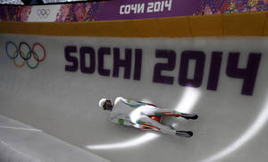 Photo - Shiva Keshavan, who is from India but competing under the Olympic Flag, completes a practice run in the men's luge singles at the 2014 Winter Olympics, Tuesday, Feb. 4, 2014, in Krasnaya Polyana, Russia. Keshavan is competing in his fifth Olympics and cannot represent India because his nation is under international  sanctions. (AP Photo/Natacha Pisarenko)
