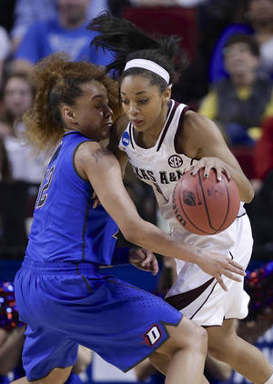 Photo - Texas A&M's Curtyce Knox, right, works against DePaul's Brittany Hrynko (12) during the first half of a regional semifinal in the NCAA women's college basketball tournament in Lincoln, Neb., Saturday, March 29, 2014. (AP Photo/Nati Harnik)