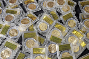 Photo - FILE - This Feb. 25, 2014 file photo shows some of the 1,427 Gold-Rush era U.S. gold coins displayed at Professional Coin Grading Service in Santa Ana, Calif. A treasure trove of rare gold coins discovered by a California couple out walking their dog is set to go on sale on Tuesday, May 27, 2014.  (AP Photo/Reed Saxon, File)