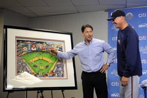 Photo -   New York Mets Chief Operating Officer Jeff Wilpon points out details on a 48 x 40 inch framed piece of artwork by Charles Fazzino that Wilpon presented to Chipper Jones during a news conference before a baseball game between the Atlanta Braves and New York Mets on Friday, Sept. 7, 2012, at Citi Field in New York. The art work highlights Jones's career at Shea Stadium. (AP Photo/Kathy Kmonicek)