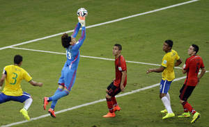 Photo - Mexico's goalkeeper Guillermo Ochoa makes a save during the group A World Cup soccer match between Brazil and Mexico at the Arena Castelao in Fortaleza, Brazil, Tuesday, June 17, 2014.  (AP Photo/Themba Hadebe)