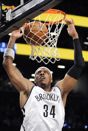 Photo - Brooklyn Nets' Paul Pierce dunks the ball during the first quarter of an NBA basketball game against the Minnesota Timberwolves Sunday, March 30, 2014, at Barclay's Center in New York. (AP Photo/Bill Kostroun)