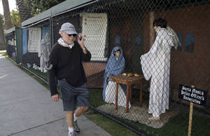 "Photo -   FILE - In this Dec. 13, 2011 file photo, a man walks past two of the traditional Nativity scenes along Ocean Avenue at Palisades Park in Santa Monica, Calif. Avowed atheist Damon Vix last year won two-thirds of the booths in the annual, city-sponsored lottery to divvy up spaces in the live-sized Nativity display. But he only put up one thing: A sign that read ""Religions are all alike - founded on fables and mythologies."" Vix left the rest of his allotted spaces empty, and in so doing, upended a Christmas tradition that began in Santa Monica nearly 60 years ago. (AP Photo/Ringo H.W. Chiu, file)"