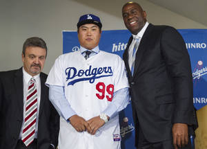 Photo - Los Angeles Dodgers general manager Ned Colletti, left, and co-owner Magic Johnson, right, present pitcher Ryu Hyun-jin, center, of South Korea, during a baseball news conference announcing his $36 million, six-year contract, Monday, Dec. 10, 2012, in Los Angeles. Ryu becomes the first player to go directly from the Korea Baseball Organization to the United States big leagues. (AP Photo/Damian Dovarganes)