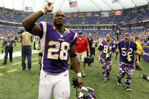 Photo - Minnesota Vikings running back Adrian Peterson celebrates as he run off the field after his team's 26-23 overtime win over the Jacksonville Jaguars in an NFL football game, Sunday, Sept. 9, 2012, in Minneapolis.(AP Photo/Genevieve Ross) <strong>Genevieve Ross</strong>