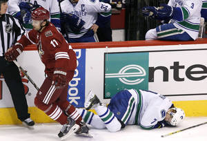 Photo - Phoenix Coyotes' Martin Hanzal (11), of the Czech Republic, skates away after knocking Vancouver Canucks' David Booth (7) to the ice, but earned a four-minute high-sticking penalty on the play, during the third period of an NHL hockey game Thursday, Jan. 16, 2014, in Glendale, Ariz.  The Coyotes defeated the Canucks 1-0. (AP Photo/Ross D. Franklin)