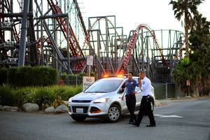 Photo - Members of the Six Flags Magic Mountain amusement park security staff monitor the situation at the exit of the park after riders were injured on the Ninja coaster Monday, July 7, 2014, in Valencia, Calif. The roller coaster hit a tree branch dislodging the front car, leaving four people slightly injured and keeping nearly two dozen summer fun-seekers hanging 20 to 30 feet in the air for hours as day turned to night. Two of the four people hurt on the Ninja coaster were taken to the hospital as a precaution, but all the injuries were minor, fire and park officials said. (AP Photo/Los Angeles Daily News, Andy Holzman)