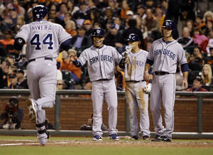 Photo - San Diego Padres' Rene Rivera (44) is greeted at the plate by teammates Alexi Amarista, center left, and Tommy Medica, right, after Rivera's three-run home run against the San Francisco Giants during the fifth inning of a baseball game Monday, April 28, 2014, in San Francisco. (AP Photo/Marcio Jose Sanchez)