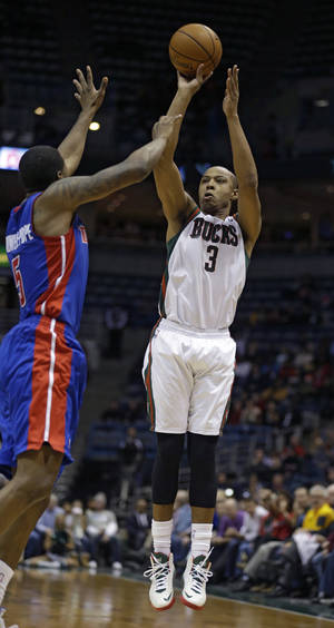 Photo - Milwaukee Bucks' Caron Butler(3) shoots against Detroit Pistons' Kentavious Caldwell-Pope, left, during the second half of an NBA basketball game Wednesday, Jan. 22, 2014, in Milwaukee. The Bucks won 104-101 and Butler scored 30 points. (AP Photo/Jeffrey Phelps)