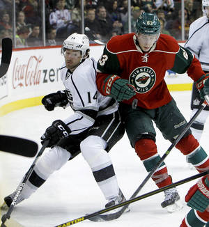 Photo - Los Angeles Kings right wing Justin Williams, left, and Minnesota Wild right wing Charlie Coyle, right, collide as they battle for the puck during the second period of an NHL hockey game in St. Paul, Minn., Tuesday, April 23, 2013. (AP Photo/Ann Heisenfelt)