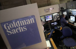 Photo - FILE - In this March 15, 2012 photo, a trader works in the Goldman Sachs booth on the floor of the New York Stock Exchange. Goldman Sachs announced Wednesday, Jan. 16, 2013 that its earnings almost tripled in the fourth quarter as investment banking revenues surged. (AP Photo/Richard Drew)