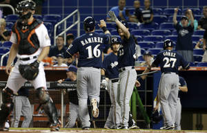 Photo - Milwaukee Brewers' Aramis Ramirez (16) is congratulated by Logan Schafer (22) after scoring on a triple by Jonathan Lucroy in the first inning of a baseball game, Wednesday, June 12, 2013 in Miami. Norichika Aoki and Carlos Gomez also scored on the play. (AP Photo/Alan Diaz)