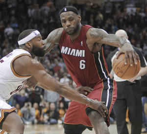 Photo - Cleveland's Baron Davis, left, defends the Heat's LeBron James on Tuesday.  AP photo