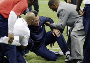 Photo - Houston Texans head coach Gary Kubiak, center, his helped after he collapsed on the field during the second quarter of an NFL football game against the Indianapolis Colts, Sunday, Nov. 3, 2013, in Houston. (AP Photo/David J. Phillip)