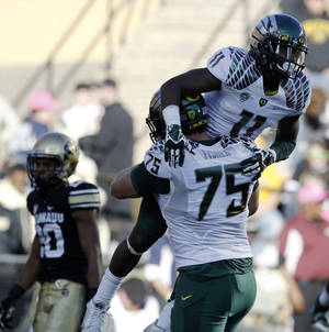 Photo - Oregon wide receiver Bralon Addison, front top, is hoisted in the air after his catch for a touchdown by offensive lineman Jake Fisher, front bottom against Colorado during the first quarter of an NCAA college football game in Boulder, Colo., on Saturday, Oct. 5, 2013. (AP Photo/David Zalubowski)