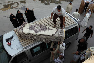 Photo - Mourners unload the coffin of Ali Abdullah who was killed in a car bomb attack, in the Shiite holy city of Najaf, 100 miles (160 kilometers) south of Baghdad, Iraq, Thursday, Aug. 15, 2013. A wave of car bombs in the Iraqi capital on Wednesday killed and wounded dozens of people, the latest attacks in a months-long surge in violence. More than 3,000 people have been killed in violence during the past few months, raising fears Iraq could see a new round of widespread sectarian bloodshed similar to that which brought the country to the edge of civil war in 2006 and 2007. (AP Photo/Haider Hamdani)