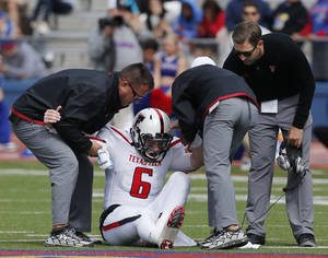 Photo - Texas Tech quarterback Baker Mayfield (6) is helped from the field by trainers and coach Kliff Kingsbury, right, during the second half of an NCAA college football game against Kansas in Lawrence, Kan., Saturday, Oct. 5, 2013. (AP Photo/Orlin Wagner)