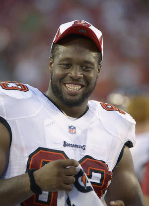 Photo - Tampa Bay Buccaneers defensive tackle Gerald McCoy (93) has a laugh on the sideline during the first half of an NFL preseason football game against the Baltimore Ravens in Tampa, Fla., Thursday, Aug. 8, 2013. (AP Photo/Phelan M. Ebenhack)