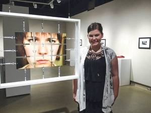"Photo - Amanda Meyer poses with her centerpiece ""At Face Value"" at her exhibit in April at Nona Jean Hulsey Gallery. Photo provided. <strong></strong>"