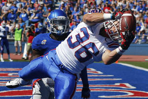Photo - Louisiana Tech running back Hunter Lee (36) makes a touchdown catch as Kansas safety Isaiah Johnson defends during the first half of an NCAA college football game in Lawrence, Kan., Saturday, Sept. 21, 2013. (AP Photo/Orlin Wagner)