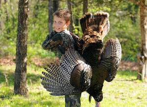 photo - Trevor Sallee, 11, of Guthrie poses with his first turkey, a 20-pound gobbler he killed with a .20 gauge shotgun during last weekend's youth turkey season. PHOTO PROVIDED