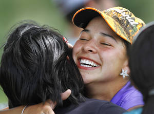 photo - GIRLS HIGH SCHOOL GOLF / STATE TOURNAMENT: Altus High School golfer Megan Blonien  breaks into a big smile as she gets a hug from supporters after she sank her putt on the 18th green to complete her round of golf during Girls Class 5A State Golf Tournament at Lincoln Park Golf Course on Wednesday, May 2,  2012.    Photo by Jim Beckel, The Oklahoman