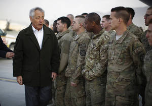 Photo - U.S. Secretary of Defense Chuck Hagel, left, greets U.S. Army troops on the tarmac of Kabul airport, March 11, 2013 before boarding a flight to Washington. Hagel encountered political tension with the Afghan president and a series of security problems during his first visit to Afghanistan as Pentagon chief, but he met privately with President Hamid Karzai and says they discussed the key issues. (AP Photo/Jason Reed, Pool)