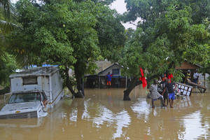 photo -   Residents of Leogane, Haiti find higher ground as the water level continues to rise Friday, Oct. 26, 2012. Residents of Leogane have had five consecutive days of rain in the aftermath of Hurricane Sandy, which caused serious flooding and claimed at least 26 lives in the impoverished country. (AP Photo/The Miami Herald, Carl Juste) MAGS OUT