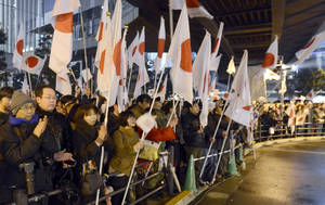 photo - In this Saturday, Dec. 15, 2012 photo, supporters of Japan's largest opposition Liberal Democratic Party (LDP) gather with national flags during a parliamentary election campaign in Tokyo. Japanese were voting Sunday, Dec. 16 in parliamentary elections that were expected to put the LDP, once-dominant conservatives, back in power after a three-year break — and bring in a more nationalistic government amid tensions with big neighbor China. (AP Photo/Kyodo News) JAPAN OUT, MANDATORY CREDIT, NO LICENSING IN CHINA, HONG KONG, JAPAN, SOUTH KOREA AND FRANCE