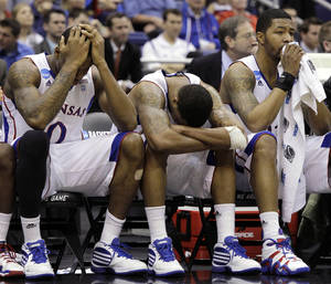 photo - From left to right, Kansas players Thomas Robinson, Marcus Morris and Markieff Morris react in the final moments against Virginia Commonwealth at the Southwest regional final game in the NCAA college basketball tournament on Sunday, March 27, 2011, in San Antonio. VCU won 71-61. (AP Photo/Tony Gutierrez) ORG XMIT: TXKJ122