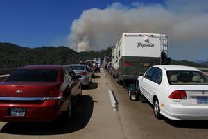 Photo - Northbound traffic comes to a standstill on the Pit River Bridge on Interstate 5 in Shasta County, Calif., as a plume of smoke rises Wednesday, Aug. 1, 2012, from the Salt Creek Fire. AP photo
