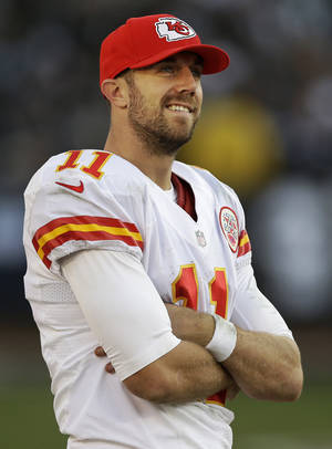 Photo - Kansas City Chiefs quarterback Alex Smith (11) smiles on the sideline during the fourth quarter of an NFL football game against the Oakland Raiders in Oakland, Calif., Sunday, Dec. 15, 2013. The Chiefs won 56-31. (AP Photo/Marcio Jose Sanchez)
