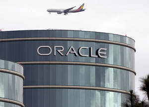 Photo - FILE - In this  Tuesday, March 20, 2012, file photo, a plane flies over Oracle headquarters in Redwood City, Calif. Oracle's latest quarterly earnings rose 18 percent as companies splurged on more software and other technology toward the end of the year.  (AP Photo/Paul Sakuma, File)