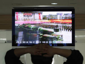 Photo - A South Korean man who is waiting to head to the North Korean city of Kaesong, watches a news program airing file footage of a North Korean rocket displayed during a military parade at the customs, immigration and quarantine office in Paju, South Korea, near the border village of Panmunjom, Thursday, April 4, 2013. North Korea's vow to restart its mothballed nuclear facilities raises fears about assembly lines churning out fuel for a fearsome arsenal of nuclear-tipped missiles. But it may actually be a sign that Pyongyang needs a lot more bomb fuel to back up its nuclear threats. (AP Photo/Ahn Young-joon)