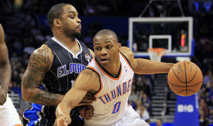 photo - Oklahoma City's Russell Westbrook, right, drives around Orlando's Jameer Nelson during the first half Thursday. Westbrook scored 29 points and had 10 assists.  AP PHOTO