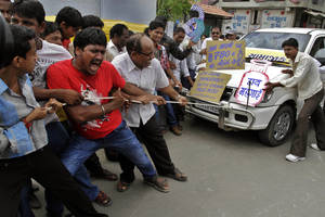 "photo -   Indian people pull a car by rope and shout slogans during a protest against the price hike in diesel and capping the number of subsidized cooking gas cylinders in Ahmadabad, India, Friday, Sept. 14, 2012. India's government is facing angry protests from its political allies as well as the opposition after it raised the price of diesel fuel in a bid to curb its ballooning fiscal deficit and also announced a reduction in cooking gas subsidies. The replica of cooking gas cylinder on the right reads as ""down with price rise."" (AP Photo/Ajit Solanki)"