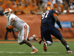 Photo - Clemson quarterback Tajh Boyd (10) runs from Syracuse defensive end John Raymon (97) during the second half of an NCAA college football game on Saturday, Oct. 5, 2013, in Syracuse, N.Y. Clemson won, 49-14. (AP Photo/Mike Groll)