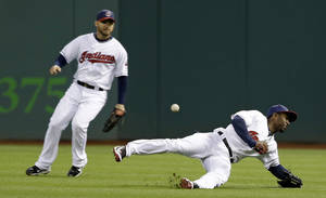 Photo - Cleveland Indians' Michael Bourn, right, dives for but cannot catch a single hit by Chicago White Sox's Alexei Ramirez in the fourth inning of a baseball game on Friday, May 2, 2014, in Cleveland. Indians' Ryan Raburn, left, watches. (AP Photo/Tony Dejak)